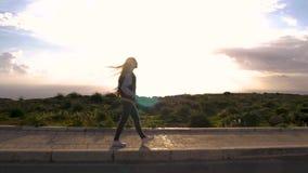 En nöjd blond flicka går säkert längs vägen, håller hennes händer i facket, modemodell med långt hår blåsigt arkivfilmer