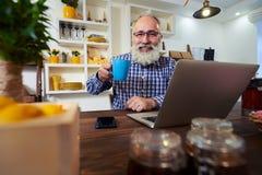 En nöjd hög man som rymmer en kopp te, medan genom att använda bärbara datorn arkivbilder