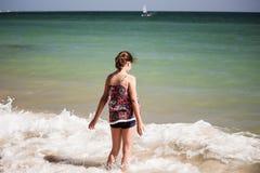 En n?tt flicka som spelar i v?gorna p? stranden, mjuk fokus, strandbegrepp royaltyfri fotografi