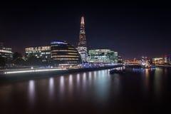 En nattsikt av den London bron och de moderna byggnaderna på den sydliga banken Fotografering för Bildbyråer