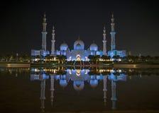 En nattsikt av Sheikh Zayed Grand Mosque från en vattenreflectio royaltyfria bilder