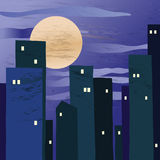 En nattstad med en stor måne Royaltyfria Bilder