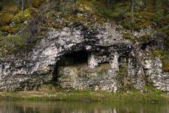 En naturlig grotta i en flodbank royaltyfri foto