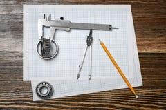 En nonieskalaklämma som rymmer ett lager, en blyertspenna och ett par av passare som ligger över skissning, skyler över brister p royaltyfri bild