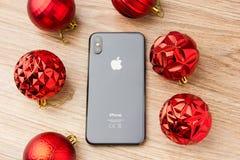 En noviembre de 2017 el iPhone 10 miente en una tabla al lado de bolas de la Navidad Imagen de archivo