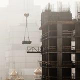 En ny bostads- byggnad under konstruktion i morgonmisten Royaltyfri Fotografi