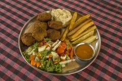 En ny falafel med stekt potatis-, hummus- och grönsaksallad med sesam, sås i en platta på tabellen med ett rutigt arkivfoton