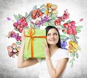 En nyfiken brunettkvinna försöker att gissa vad är insidan den gröna gåvaasken Arkivbild