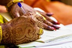 En nyligen gift indisk bengali fru med formen för registrering för förbindelse för guldbröllopcirkel den undertecknande fotografering för bildbyråer