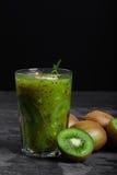 En nytt sammanpressad söt coctail från kiwi med mintkaramellen på ett stenskrivbord och på en svart bakgrund bär fruktt organiskt arkivfoto