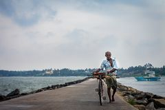 En obekant äldre man bär en cykel längs kusten av havet arkivbilder