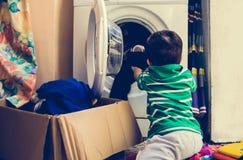 En och de gamla halva åren behandla som ett barn pojken som sätter kläder i tvagningmaskin royaltyfri bild