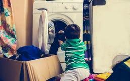 En och de gamla halva åren behandla som ett barn pojken som sätter kläder i tvagningmaskin arkivfoto