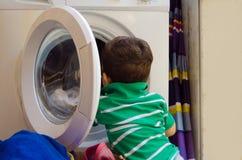 En och de gamla halva åren behandla som ett barn pojken som sätter kläder i tvagningmaskin fotografering för bildbyråer