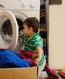 En och de gamla halva åren behandla som ett barn pojken som sätter kläder i tvagningmaskin royaltyfri foto