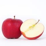 En och en halv röda äpplen över vit bakgrund royaltyfri foto