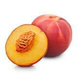 En och halv röd persika som isoleras på vit Arkivfoton