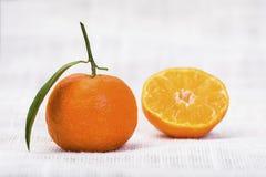 En och en halv tangerin med bladet fotografering för bildbyråer