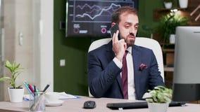 En oficina de negocios creativa el hombre de negocios joven tiene una conversación otra el teléfono almacen de metraje de vídeo