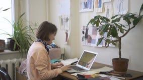 En oficina el diseñador de moda de sexo femenino trabaja en un ordenador portátil almacen de metraje de vídeo