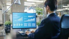 En oficina el hombre de negocios trabaja en su escritorio en un Comput personal fotografía de archivo