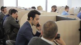 En oficina los hombres trabajan en trajes de negocios y comunican por el teléfono metrajes