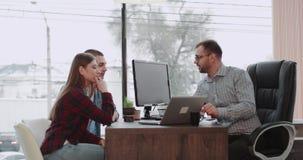 En oficina panorámica hermosa los pares jovenes tienen una reunión con su agente inmobiliario o director de banco para conseguir  almacen de metraje de vídeo