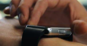 En oficina un hombre que usa su smartwatch El primer extremo da tecnología digital del dispositivo metrajes