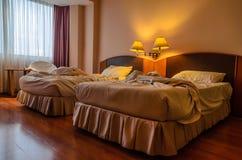 En ogjord säng av ett hotellrum Royaltyfria Bilder