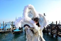 En oidentifierad kvinna i den vita maskeradkläderna med enorma vita fjädrar påskyndar under Venedig Cernival Royaltyfri Foto