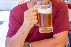 En oidentifierad man dricker ut ur ett stort exponeringsglas rånar av ljust öl på bakgrunden av en bar på en trätabell arkivfoton