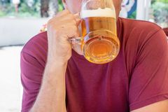 En oidentifierad man dricker ut ur ett stort exponeringsglas rånar av ljust öl på bakgrunden av en bar på en trätabell royaltyfri foto