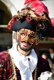 En oidentifierad man i röd maskeradkläder och maskering har en stor svart hatt med röda fjädrar under den Venedig karnevalet Arkivbild
