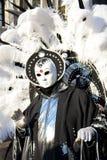 En oidentifierad man i svart maskeradkläder med enorma vita fjädrar på baksidan bär en vit maskering under Venedig Cernival Royaltyfri Bild