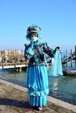 En oidentifierad man klär utarbetade azura och svarta maskeradkläder nära den Venetian lagun under den Venedig karnevalet Arkivfoto