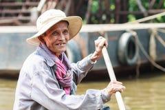 En oidentifierad man ler Kompong Phluk som paddlar ett fartyg Arkivfoton