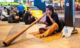 En oidentifierad man som spelar musikinstrumentet på gatan Arkivbilder