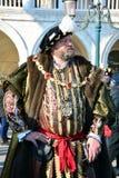 En oidentifierad man står i piazza San Marco som är iklädd en kunglig maskeradkläder under den Venedig karnevalet Arkivfoto
