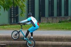 En oidentifierad ung man eller mountainbiker vid smutsbanhoppning på stentrappa utomhus arkivbild