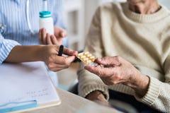 En oigenkännlig vård- besökare som förklarar en hög kvinna i rullstol hur man tar piller royaltyfri bild