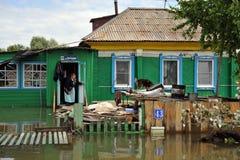 En okänd äldre kvinna i henne hem under en flod Obet River, som kom ut ur bankerna, översvämmade utkanten av staden Fotografering för Bildbyråer