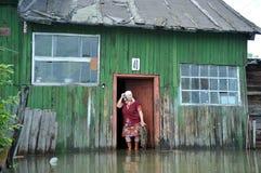 En okänd äldre kvinna i henne hem under en flod Obet River, som kom ut ur bankerna, översvämmade utkanten av staden Arkivbilder