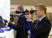 En okänd man ser i en optisk sikt på den internationella utställning`-Interpolitex `en, royaltyfri bild