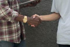 En olik färghandskakning, en svart och handskakning för handshaking för yelow vit och svart, arkivfoto
