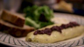 En omlette på en vit platta med skivad bröd och sallad lager videofilmer