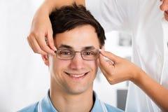 En optiker Helping Male Patient med nytt glasögon Fotografering för Bildbyråer