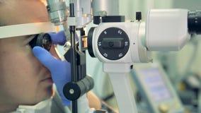 En optiker rymmer en lins för att undersöka baksidan av patientögat arkivfilmer