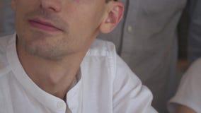 En orakad man i en vit skjorta arbetar som ett lag, en kontorsarbetare close upp arkivfilmer