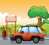 En orange bil längs gatan med en träskylt Arkivfoto