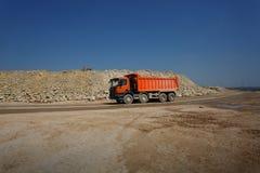 En orange dumper, lastbil mycket av stenar i ett sandvillebråd, transportering av material på en naturlig bakgrund royaltyfri fotografi